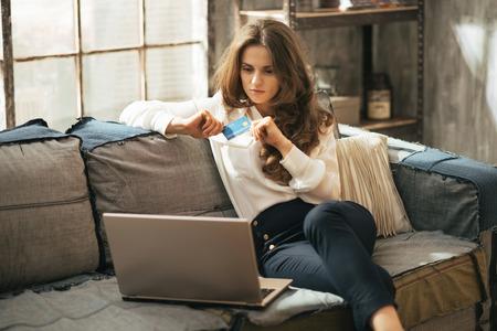 Mujer joven con tarjeta de crédito usando la computadora portátil en el apartamento tipo loft Foto de archivo