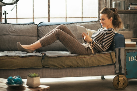 Happy young woman laying on divan and using tablet pc in loft apartment