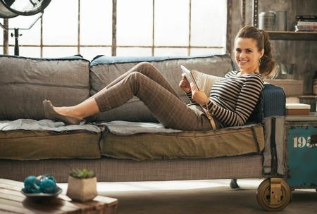 Lachende jonge vrouw die op divan en met behulp van tablet pc in de loft appartement