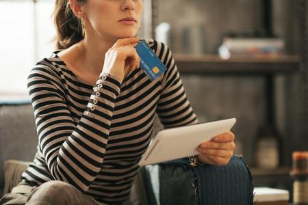 divan: Closeup auf nachdenkliche junge Frau mit Kreditkarte und Tablet PC auf Diwan sitzend