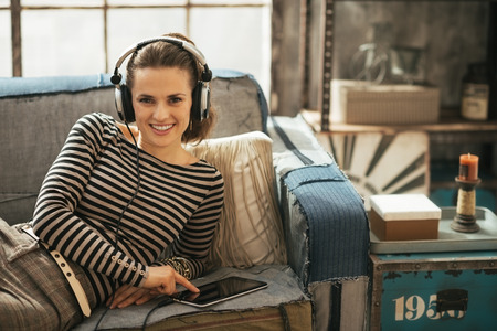 Happy young woman listening music in headphones while laying on sofa photo