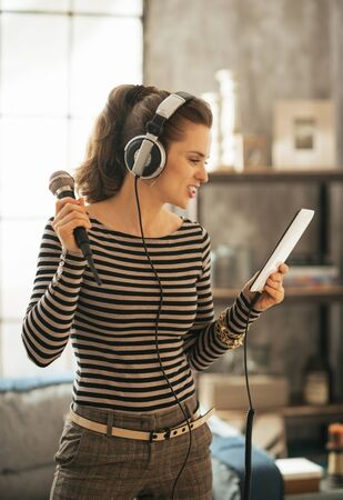 karaoke: Young woman with tablet pc singing karaoke Stock Photo