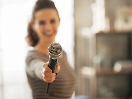 Closeup on young woman stretching microphone in camera photo