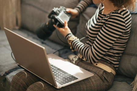 Closeup on young woman with laptop using modern dslr photo camera photo