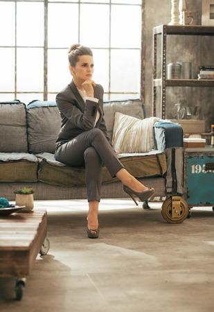 divan: Durchdachte Gesch�ftsfrau sitzt auf dem Sofa im Loft-Wohnung