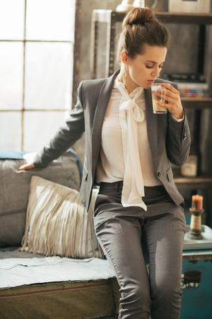 divan: Gesch�ftsfrau mit Kaffee Latte sitzt auf Sofa in Loft-Wohnung