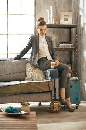 divan: In voller L�nge Portrait der Gesch�ftsfrau mit Kaffee Latte sitzt auf Sofa in Loft-Wohnung Lizenzfreie Bilder