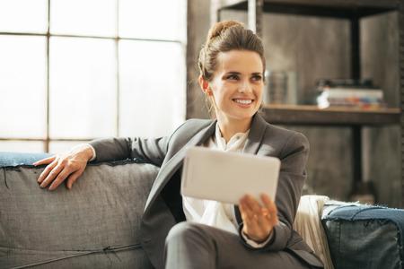 divan: Mujer de negocios feliz sentado en el sof� en el apartamento tipo loft y con la PC de la tableta Foto de archivo