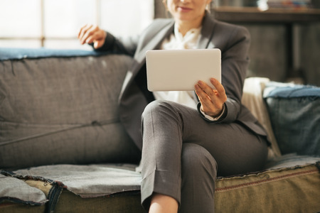 Closeup on business woman sitting on divan in loft apartment and using tablet pc photo