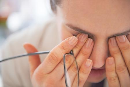 Close-up op moe zakelijke vrouw met bril