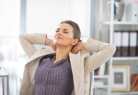 Relaxed business woman in office Imagens