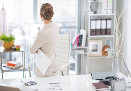 Business woman standing with document in office. rear view Фото со стока