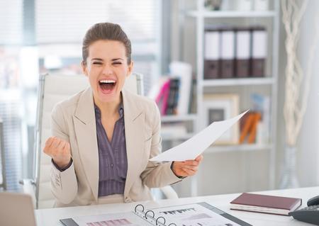 mujeres trabajando: Mujer de negocios feliz con el documento regocijo