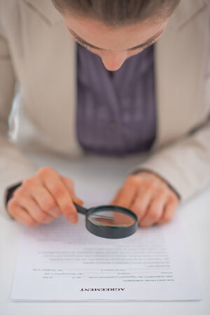suspiciousness: Closeup on business woman exploring document with magnifying lens