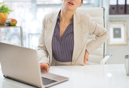 manager office: Closeup on business woman with back pain