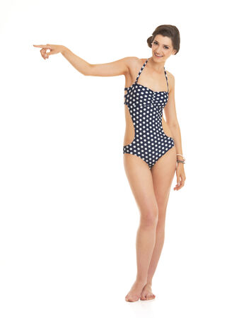 Full length portrait of happy young woman in swimsuit pointing on copy space photo