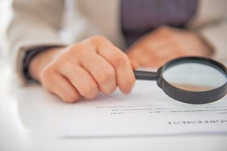 Close-up op zakenvrouw verkennen document met vergrootglas