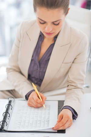 Portrait of business woman writing in document Stock Photo - 29947770