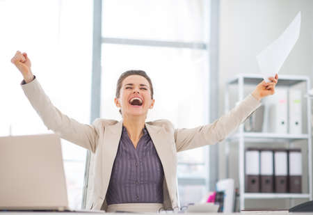 Happy business woman with document rejoicing at work Stock Photo