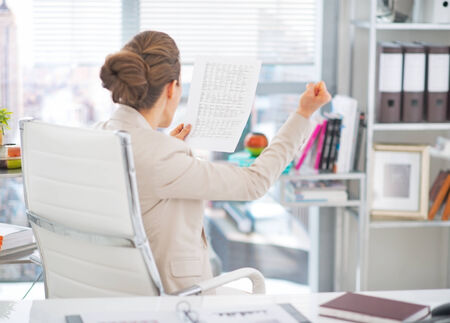 Happy business woman with document rejoicing at work. rear view Stock Photo - 29947775