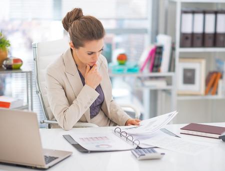 Doordachte zakenvrouw documenten in office Stockfoto - 29947776