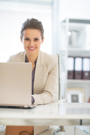 Happy business woman working on laptop in office