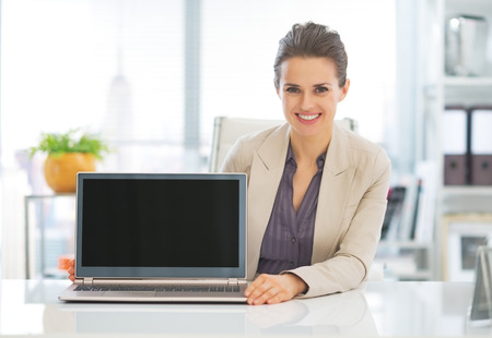 Happy business woman showing laptop blank screen Stock Photo - 29996960