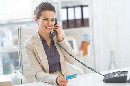 Smiling business woman talking phone in office Stock Photo - 29996966