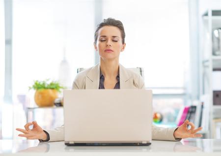 Business woman meditating near laptop Stock Photo - 29996975