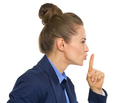 Profile portrait of business woman showing shh gesture photo
