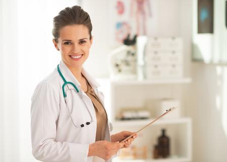 Retrato de mujer médico con portapapeles en la oficina Foto de archivo