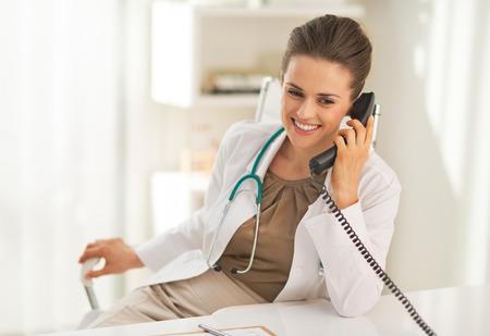 Happy doctor woman talking phone Archivio Fotografico
