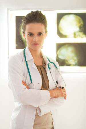 Portrait of confident doctor woman in front of lightbox