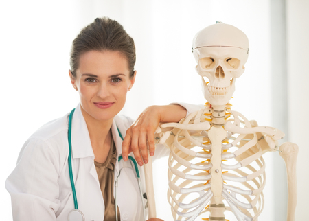 anatomical model: Portrait of doctor woman near human skeleton anatomical model Stock Photo