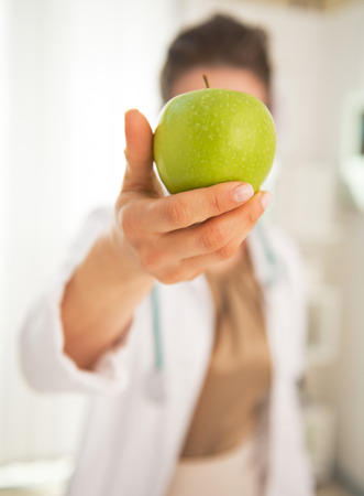 Closeup on doctor woman showing apple in front of face Stock Photo - 30972940