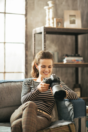 divan: Happy young woman sitting on divan and using modern dslr photo camera