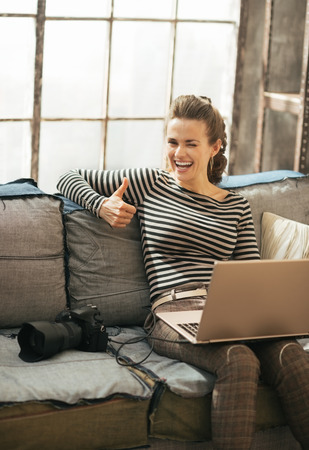 Young woman with laptop and modern dslr photo camera showing thumbs up photo