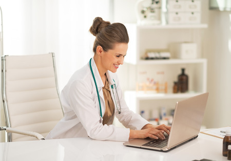 topicality: Doctor woman working on laptop in office