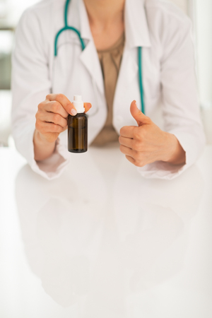 Closeup on doctor woman showing medicine bottle and thumbs up photo