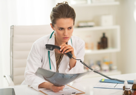 disquieted: Concerned doctor woman with fluorography holding phone