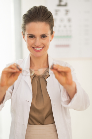 doctor giving glass: Doctor woman giving eyeglasses in front of snellen chart Stock Photo