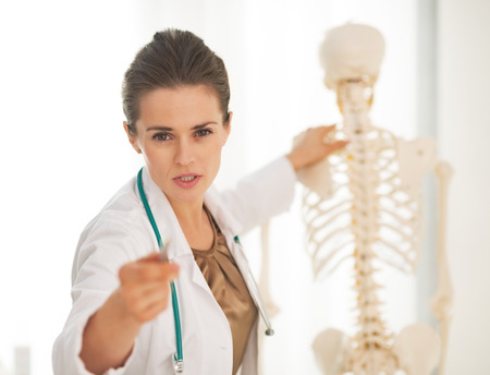 Doctor woman showing on spine and pointing in camera photo