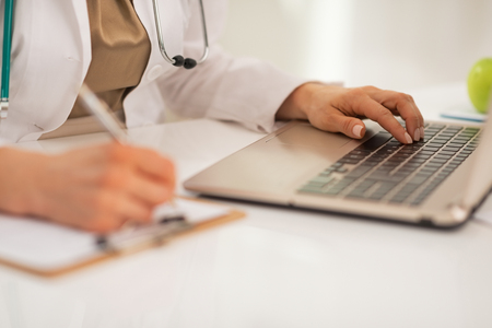 topicality: Closeup on doctor woman working on laptop in office
