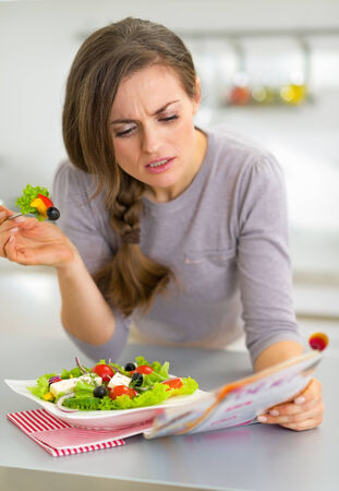 Young woman eating greek salad in kitchen and reading magazine Stock Photo