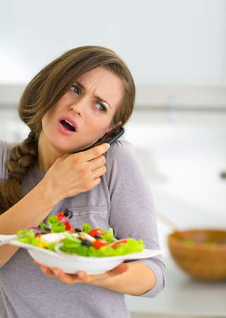 disquieted: Concerned young woman with vegetable salad talking mobile phone Stock Photo