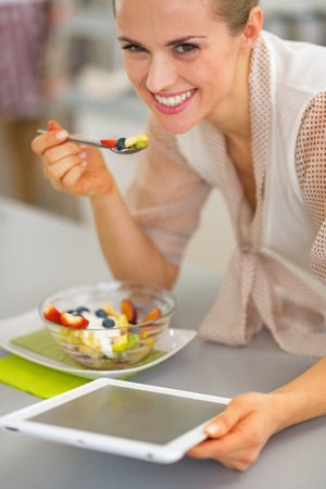 topicality: Happy young woman eating fruit salad and using tablet pc