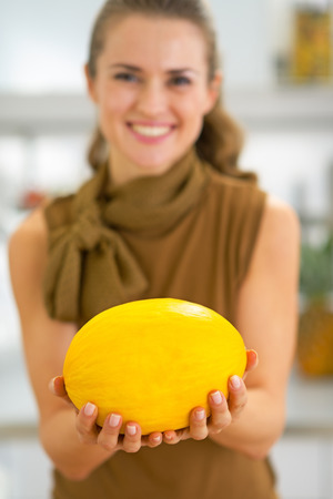 Closeup on happy young woman showing melon photo