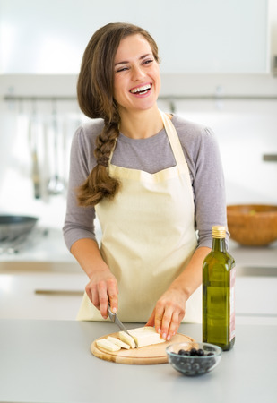 Happy young housewife cutting cheese in kitchen photo