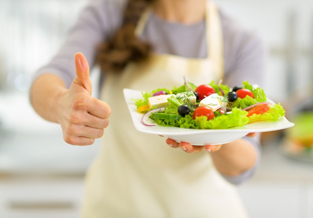 Closeup on young housewife showing greek salad and thumbs up photo