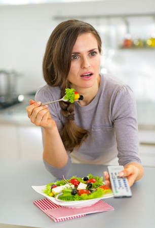 Surprised young woman eating greek salad and watching tv photo
